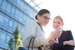 Low angle view of happy businesswomen using smart phone Stock Photos