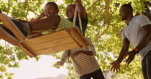Low angle view of happy family playing on the swings. In a park stock video
