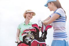 Low angle view of happy female golfers talking against clear sky Royalty Free Stock Photos