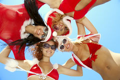 Low angle view of happy girls in christmas suit. Standing together in a circle against blue sky Royalty Free Stock Photos