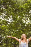 Low angle view of happy woman with arms raised in park Royalty Free Stock Image