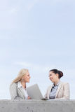 Low angle view of happy young businesswomen with laptop discussing while standing on terrace against sky Royalty Free Stock Image