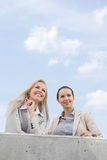 Low angle view of happy young businesswomen looking away while standing on terrace against sky Royalty Free Stock Images