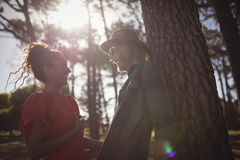 Low angle view of happy young couple looking at each other while standing together at forest Stock Photography