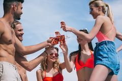 low angle view of happy young friends clinking glasses of royalty free stock image