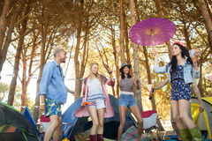 Low angle view of happy young friends dancing at campsite Stock Photos
