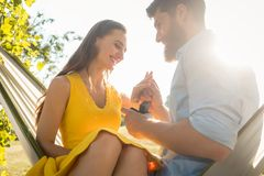 Happy man putting engagement ring on the finger of girlfriend on. Low-angle view of a happy young men putting an engagement ring on the finger of his girlfriend royalty free stock image