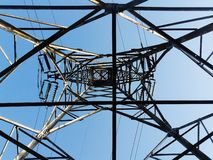 Low angle view of a high electricity pillar   from inside against blue sky royalty free stock photography