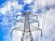 High Voltage Tower  Structure and Power Lines Against Blue Cloudy Sky. Low Angle View of High Voltage Tower  Structure and Power Lines Against Blue Cloudy Sky stock photography