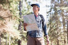 Low angle view of hiker with map standing in forest Stock Photos