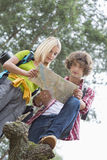Low angle view of hiking couple reading map together in forest Royalty Free Stock Image