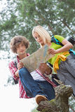 Low angle view of hiking couple reading map together in forest Stock Photography