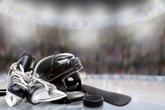 Ice Hockey Helmet, Skates, Stick and Puck in Rink. Low angle view of hockey helmet, skates; stick and puck on ice with deliberate shallow depth of field on stock photo