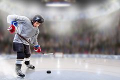 Junior Hockey Player Puck Handling in Arena. Low angle view of hockey player handling puck on ice with sports arena full of fans in the stands and copy space stock images