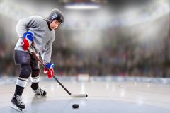 Junior Hockey Player Puck Handling in Arena. Low angle view of hockey player handling puck on ice with sports arena full of fans in the stands and copy space royalty free stock photos