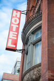 Red Hotel Sign. Low angle view of a hotel sign outside the window of a Victorian hotel stock photo