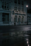Low angle view of impressive classical building. Veritcal close up low angle view of impressive classical concrete building's numerous windows on a wet night Stock Image