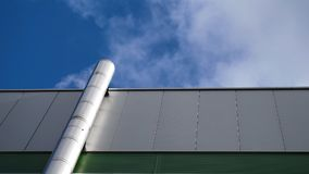 Low angle view of industrial factory chimney with grey smoke over bright sunny sky in England stock photo