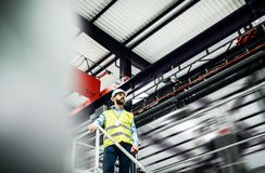 A low angle view of an industrial man engineer standing in a factory. stock photo