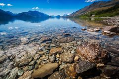 Low angle view from the shore of Lake Wakatipu, New Zealand. Low angle view at Lake Wakatipu with snow capped mountains and Pig and Pigeon Islands in the Stock Photography
