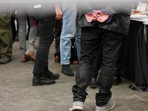 Low angle view of the legs of a crowd of men. In diverse clothing and fashions standing or walking at a public venue or meeting Royalty Free Stock Photography