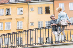 Low angle view of loving middle-aged couple by railing against building Stock Photos