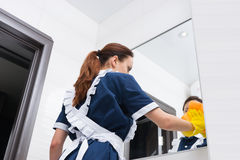 Low angle view on maid cleaning mirror Stock Photos