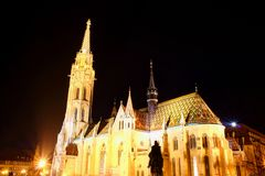 Floodlit Matthias Church low angle night view Budapest Hungary. Low angle view of majestic tall Matthias Church floodlit by exterior facade lights with King royalty free stock image