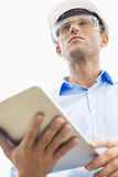Low angle view of male architect holding tablet PC against sky royalty free stock image