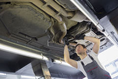 Low angle view of male automobile mechanic repairing car in repair shop Royalty Free Stock Images