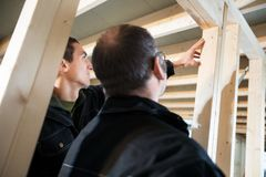 Low Angle View Of Carpenters Analyzing Wood In Incomplete Buildi stock photography