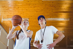 Low angle view of male coach advising female basketball player. While practicing in court Royalty Free Stock Photo