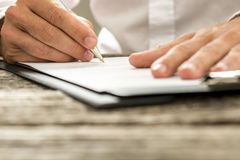 Low angle view of male hand signing contract or subscription for. M with a pen on a rustic wooden desk Royalty Free Stock Images