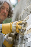 Low angle view of male worker pressing an ornamental tile into a. Glue on a wall with his hands in protective gloves Stock Photography