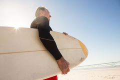 Low angle view of man carrying surboard while standing at beach Stock Images