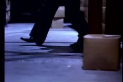 Low angle view of man chasing suspect in warehouse