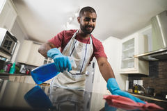 Low angle view of man cleaning marble counter in kitchen Stock Photo