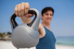 Low angle view of man holding kettlebell at beach. Low angle view of young man holding kettlebell at beach Royalty Free Stock Photos