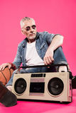 Low angle view of man in sunglasses sitting near tape recorder and basketball ball Royalty Free Stock Image