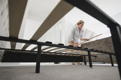 Mature Woman Building Bed in New Home Stock Image