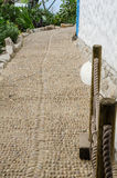 Low Angle View of Mediterranean Pebble Cobble Path White Wall an. D Garden Royalty Free Stock Photography