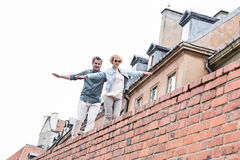 Low angle view of middle-aged couple with arms outstretched walking on brick wall against clear sky Stock Images