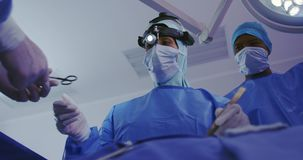 Low angle view of Middle-east female surgeon performing surgery in operation theater at hospital stock video footage