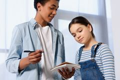 Low angle view of multicultural friends looking at notebook. At home royalty free stock photo