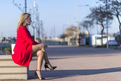 Free Low Angle View Of A Elegant Blonde Woman In Red Jacket Sitting On A Bench Outdoors While Looking Away In Sunny Day Royalty Free Stock Photo - 159094665