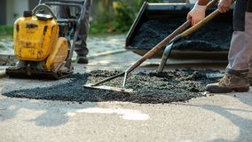 Free Low Angle View Of Two Workers Arranging Fresh Asphalt Mix With Rakes And Shovel Royalty Free Stock Photos - 136091828