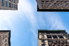 Low angle view of old apartment buildings in Tribeca. New York. Directly below view against blue sky stock images