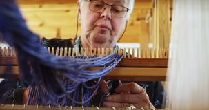 Low angle view of old caucasian senior woman preparing and sitting at hand loom machine in a worksho stock footage