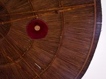 Low angle view of a parasol with red lamp in straw wicker pattern of lines and bright sky stock photos