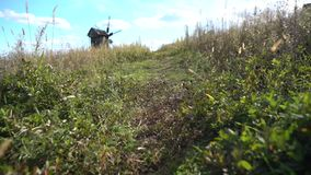 Pathway over a grassy hill leading to a windmill stock video